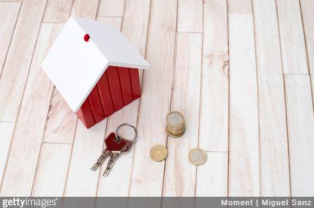 Petite maison en bois avec des clés et des pièces de monnaie
