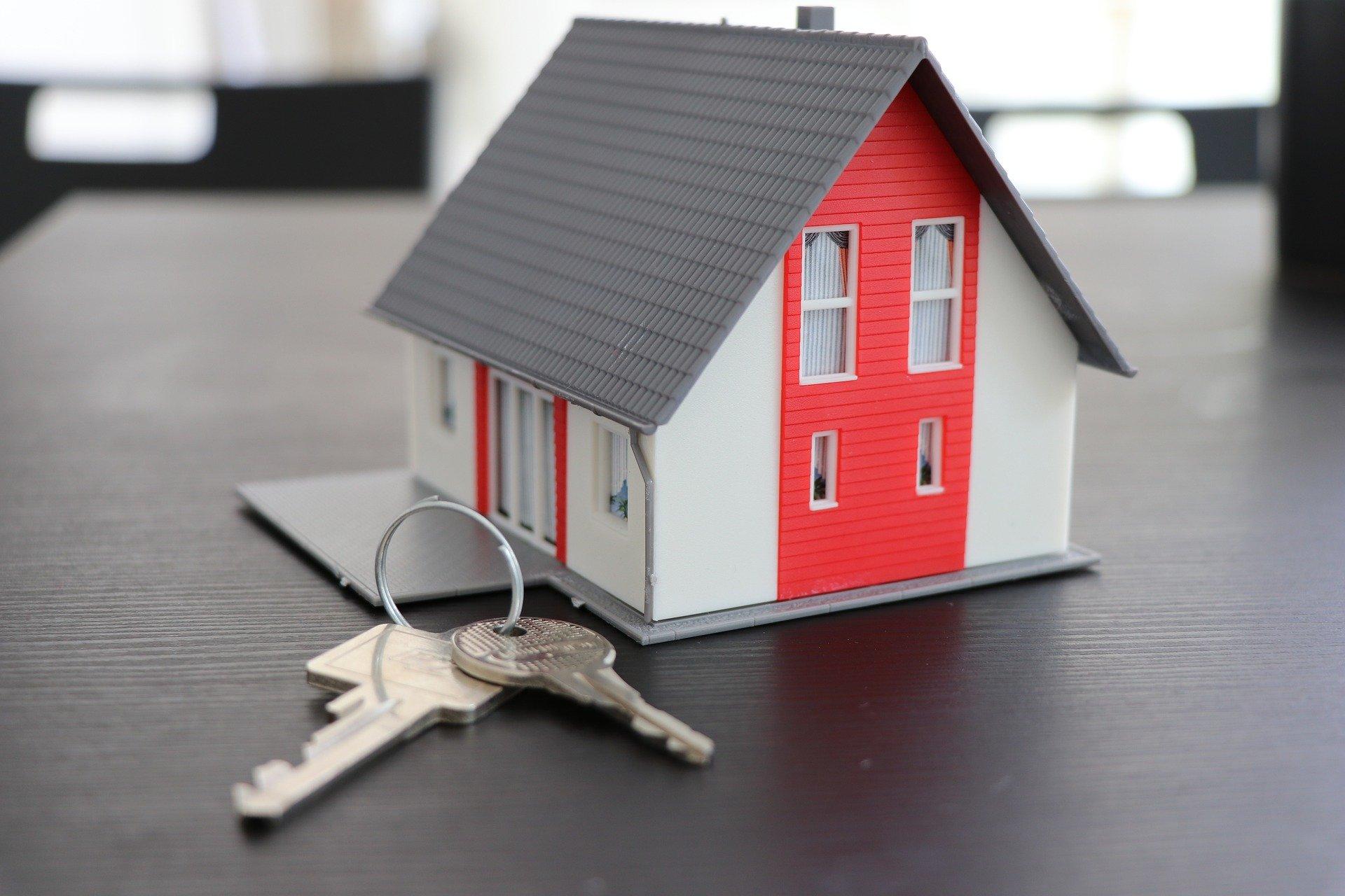 Clés posées sur une table à côté desquelles se trouve une maison miniature