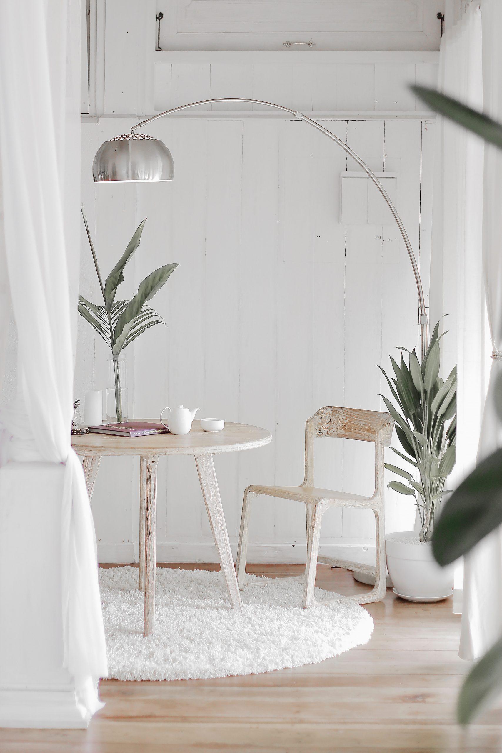 pièce décorée en blanc avec parquet au sol table e t chaise en bois luminaire et plantes