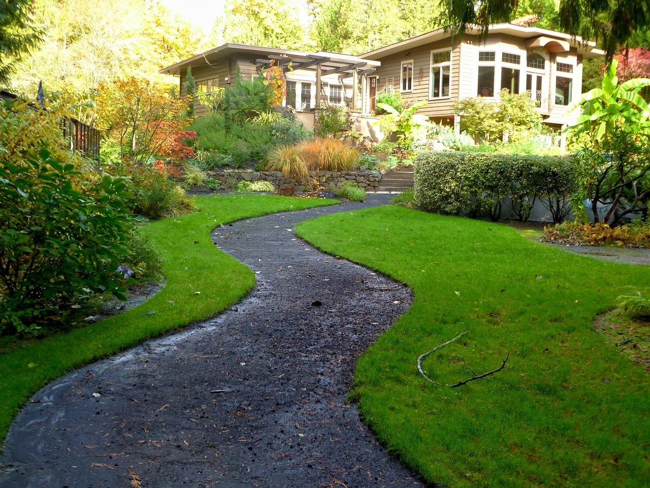 Jardin avec une allée menant à une grande maison