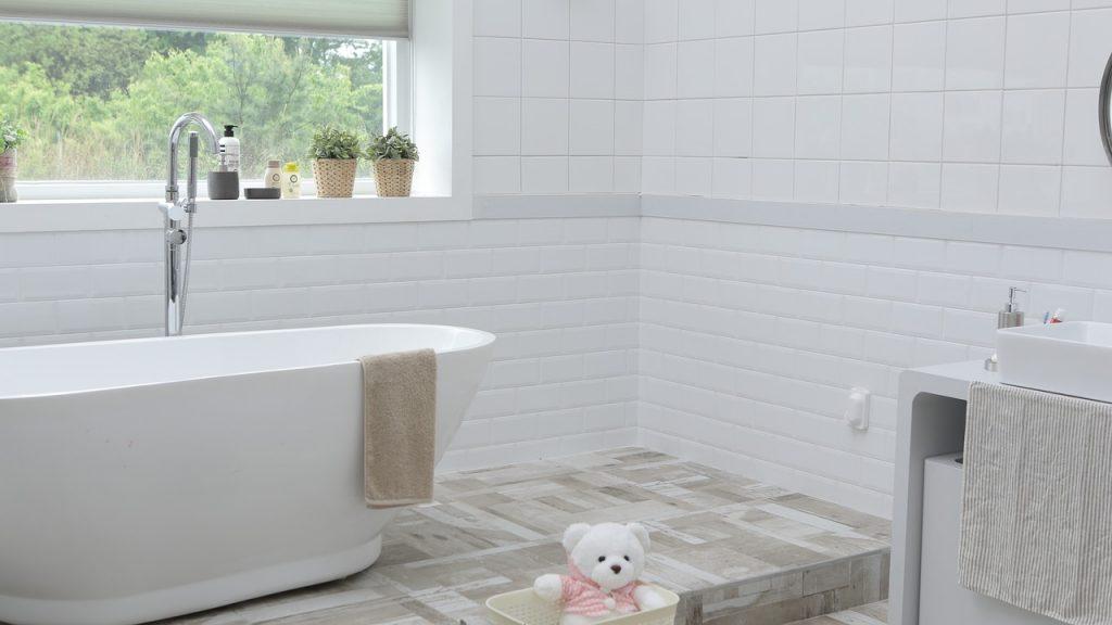 salle de bain avec baignoire carrelage mural blanc et sol effet parquet